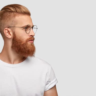 Profile shot of handsome male with trendy hairdo and beard, looks aside with serious expression, has thick red beard, wears round glasses, focused into distance, isolated over white background