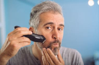 middle aged man shaving his beard against blue background