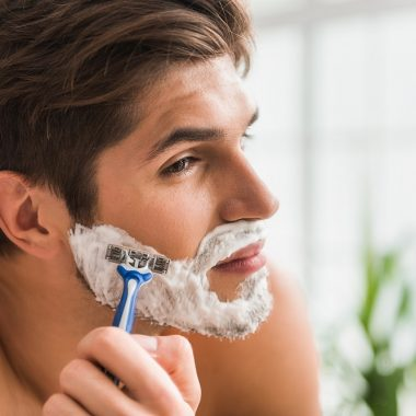 Serious guy shaving
