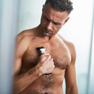 man shaving chest after shower